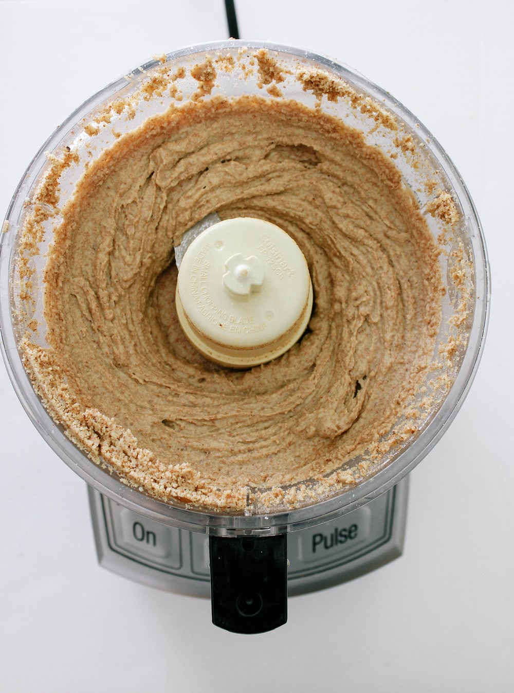 top down view of homemade almond butter after processing in a food processor for about 15 minutes, beginning to become smooth