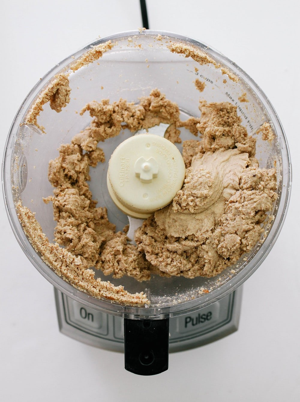 top down view of homemade almond butter in a food processor after being processed for about 10 minutes, clumpy in formation