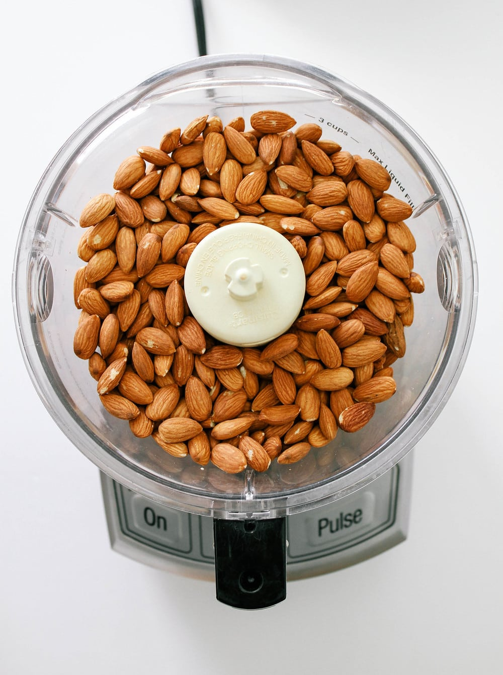 almond added to the bottom of a food processor before starting to blend