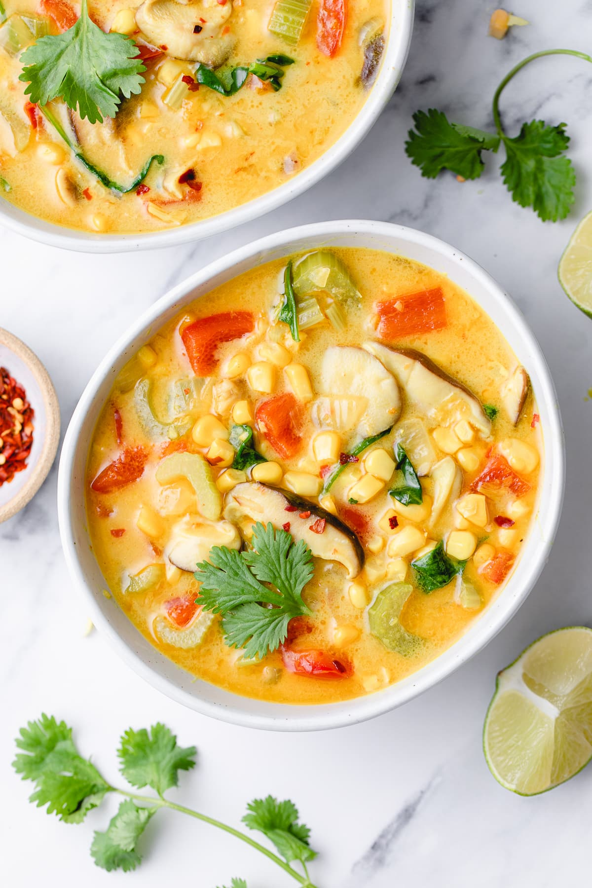 top down view of plated thai coconut curry corn soup with items surrounding.