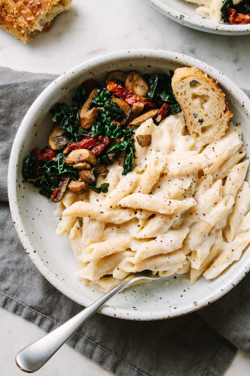 vegan white bean cauliflower alfredo sauce with penne pasta in a bowl with sauteed kale, mushrooms and sun-dried tomatoes.