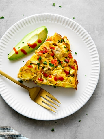 top down view of a slice of vegetable vegan frittata on a small white plate with fork and avocado.