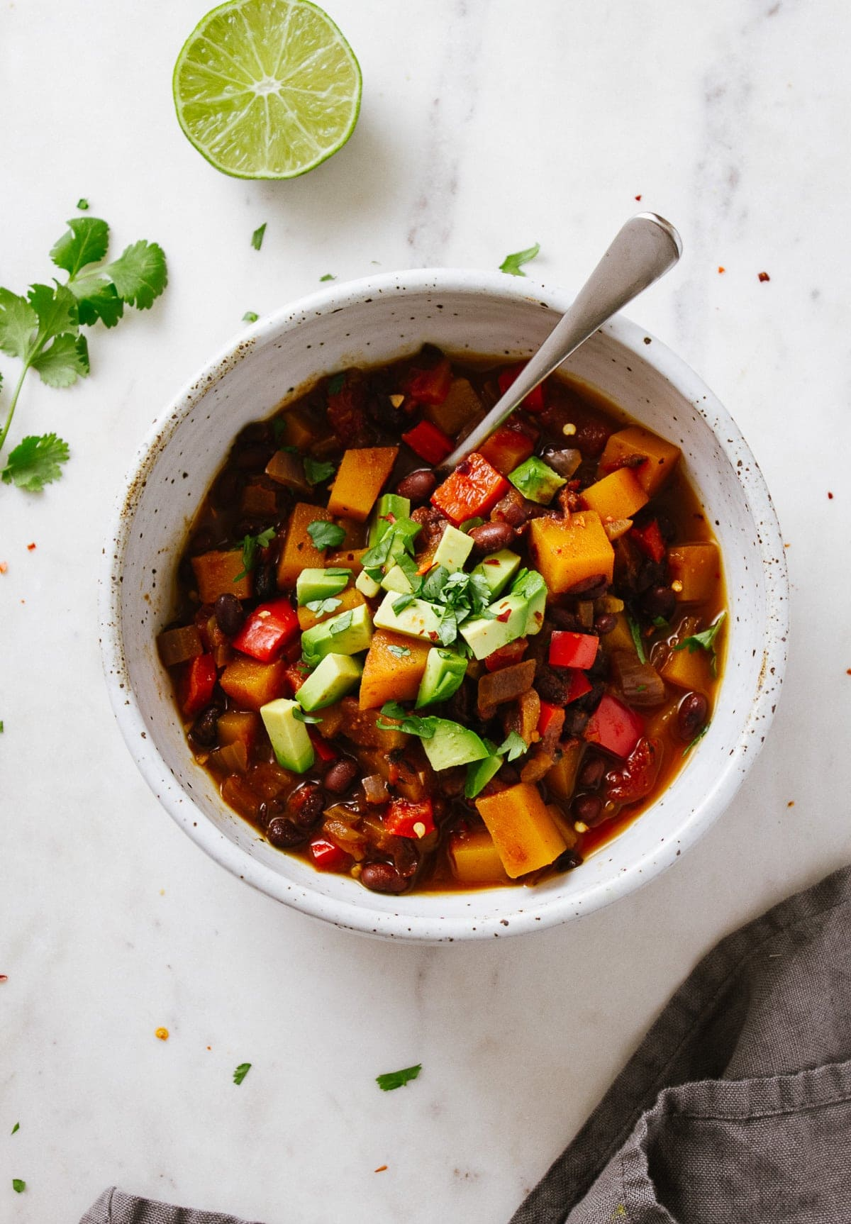 top down view of black bean and butternut squash chili in a serving bowl with spoon.