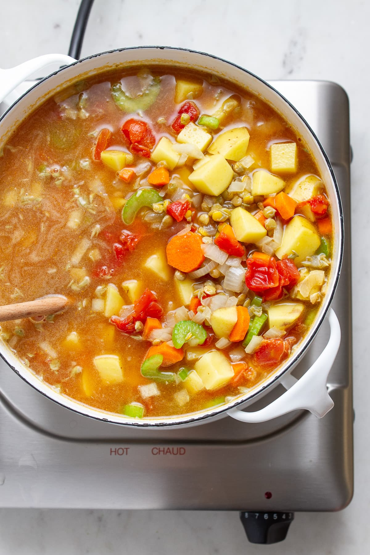 top down view of a pot full of curry lentil soup ready to simmer.