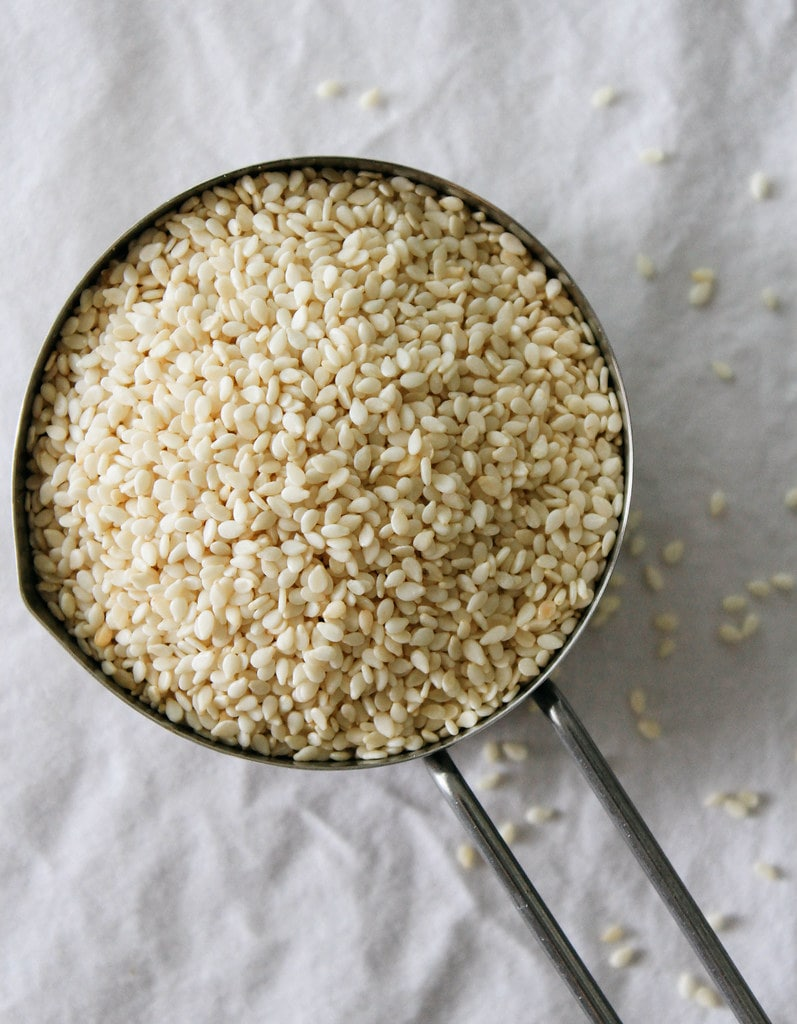top down view of white sesame seeds in a measuring cup