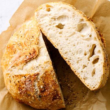 no knead bread cut in half on parchment paper