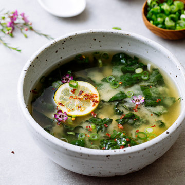 side angle view of bowl with serving of garlic miso soup with kale and items surrounding.