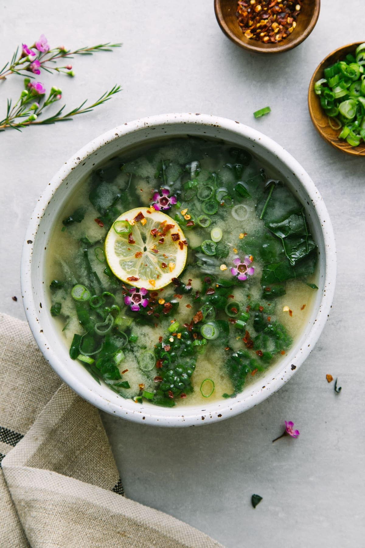 top down view of bowl with serving of garlic miso soup with kale and items surrounding.