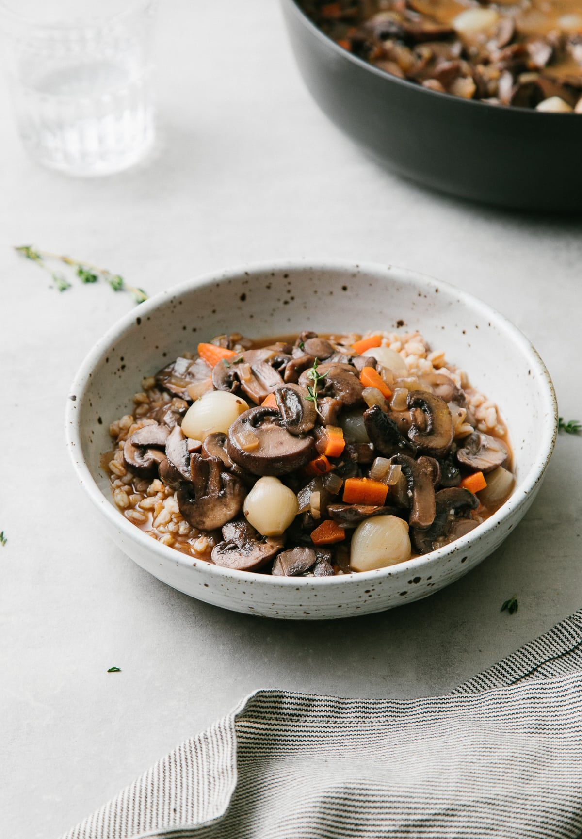 side anlge view of handmade bowl with a serving of mushroom bourguignon and farro with items surrounding.