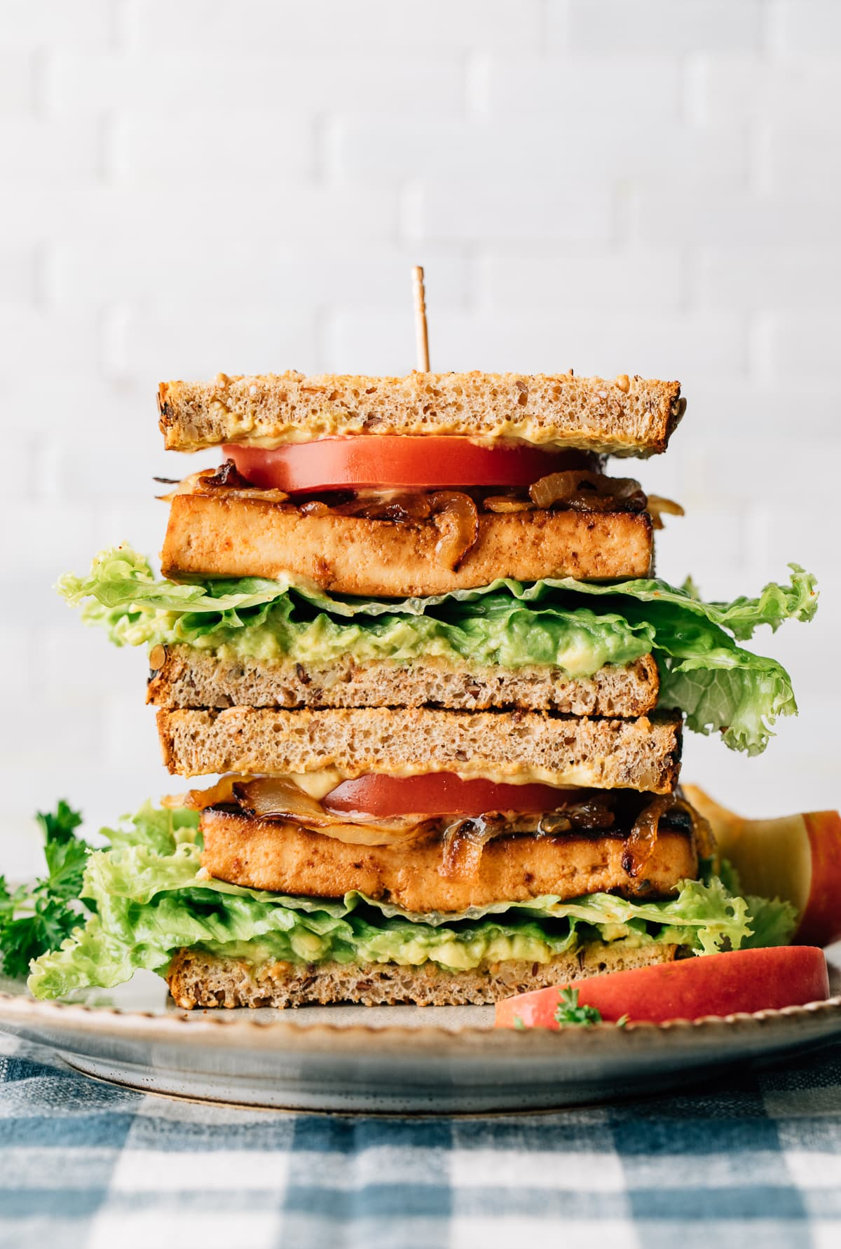 head on view of two halves of tofu sandwich stacked on a plate.