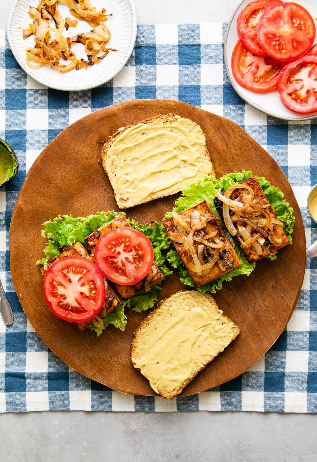 top down view showing the process of layering tofu sandwich with ingredients.