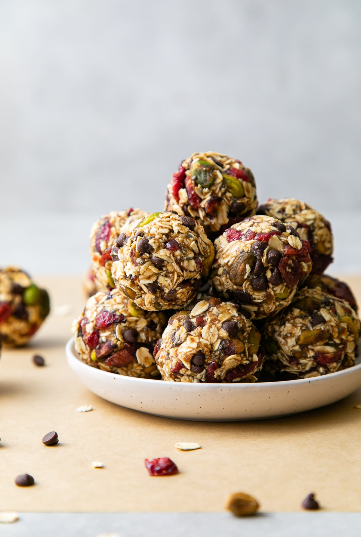 head on view of freshly rolled oatmeal energy bites with pistachios and cranberries on a plate.