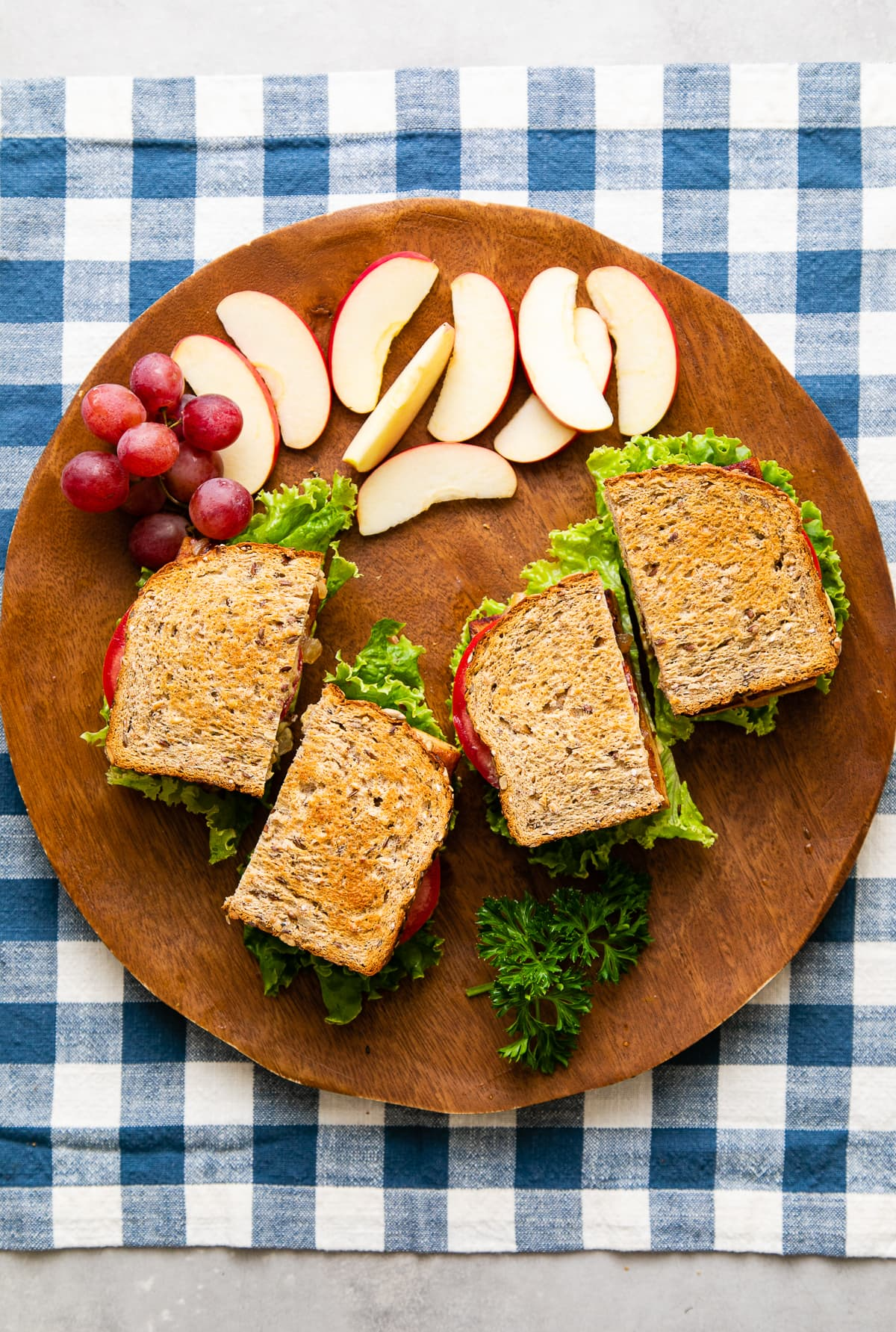 top down view of tofu sandwiches sliced in half on wooden tray with fruit.