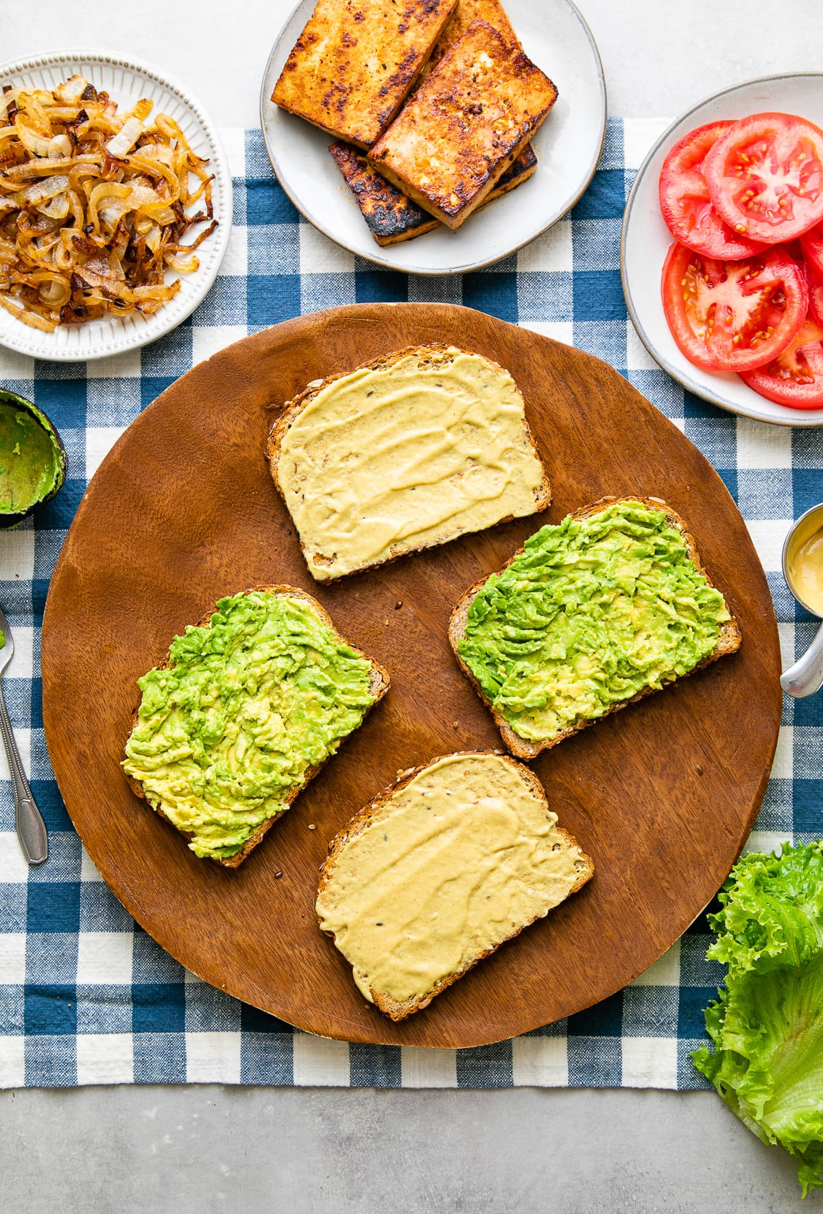 top down view showing bread slices slathered with dijon and avocado.