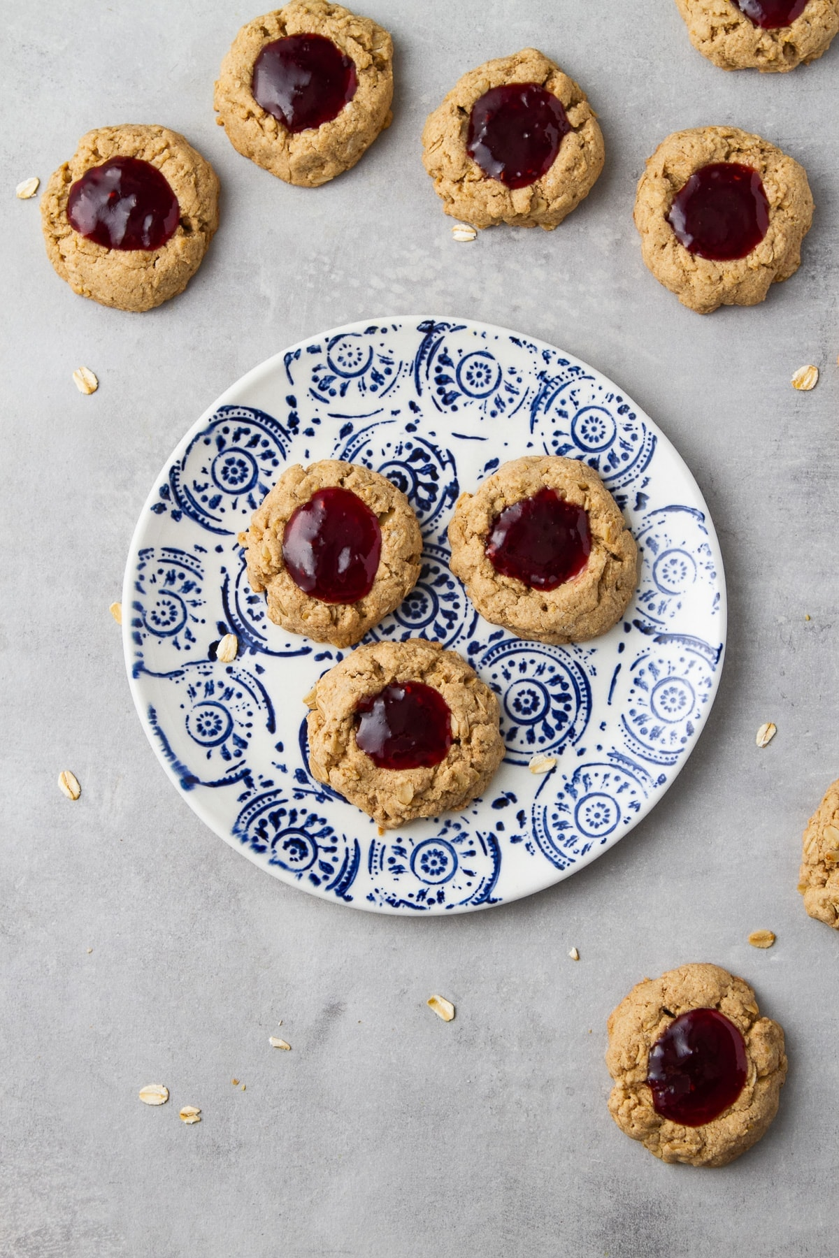 top down view of freshly made vegan oat jam thumbprint cookies on a small plate.