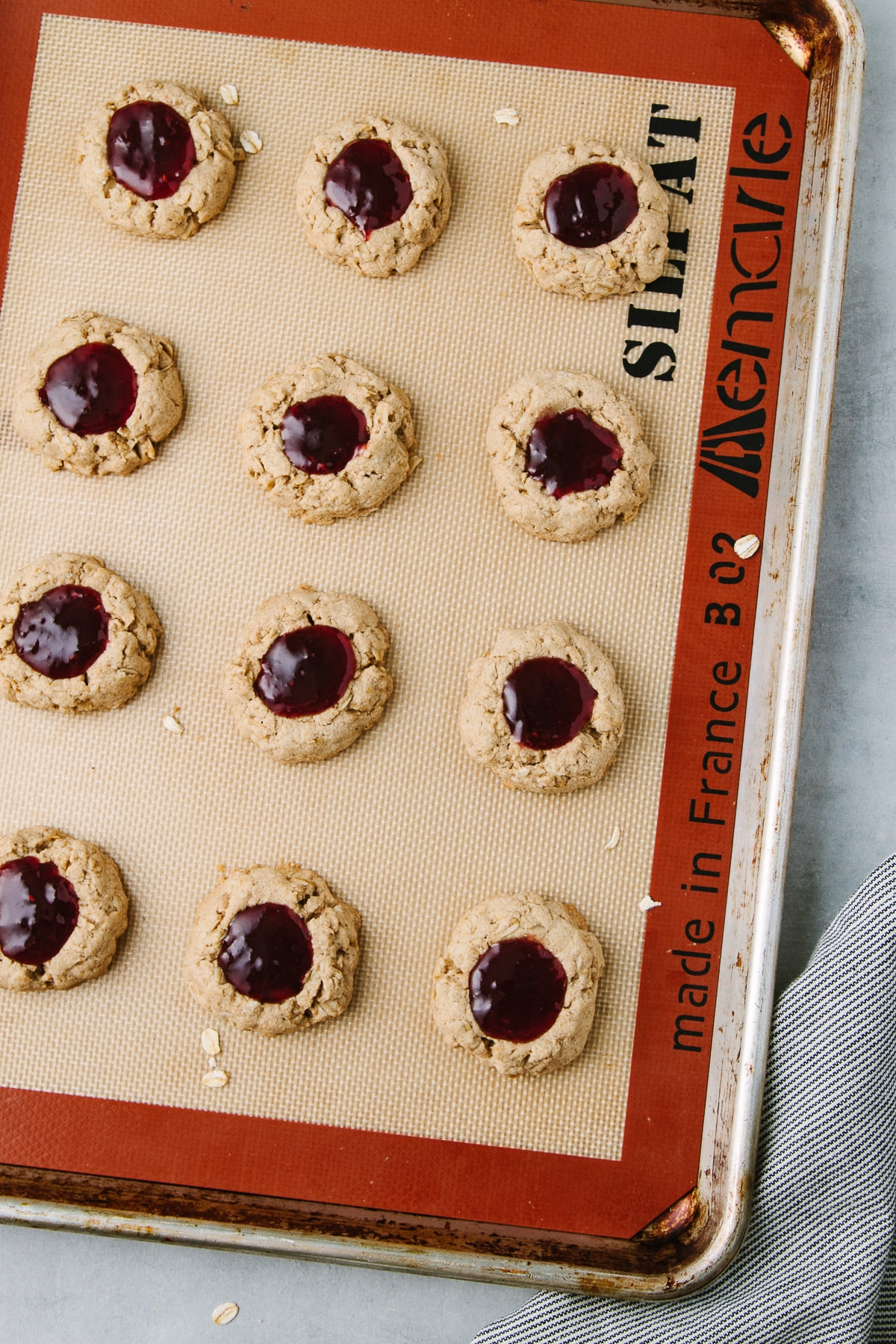top down view of healthy vegan thumbprint cookies on a rimmed a baking sheet.