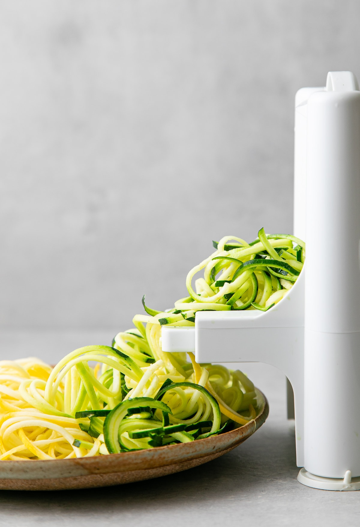 head on view of showing the process of making raw zucchini noodles.