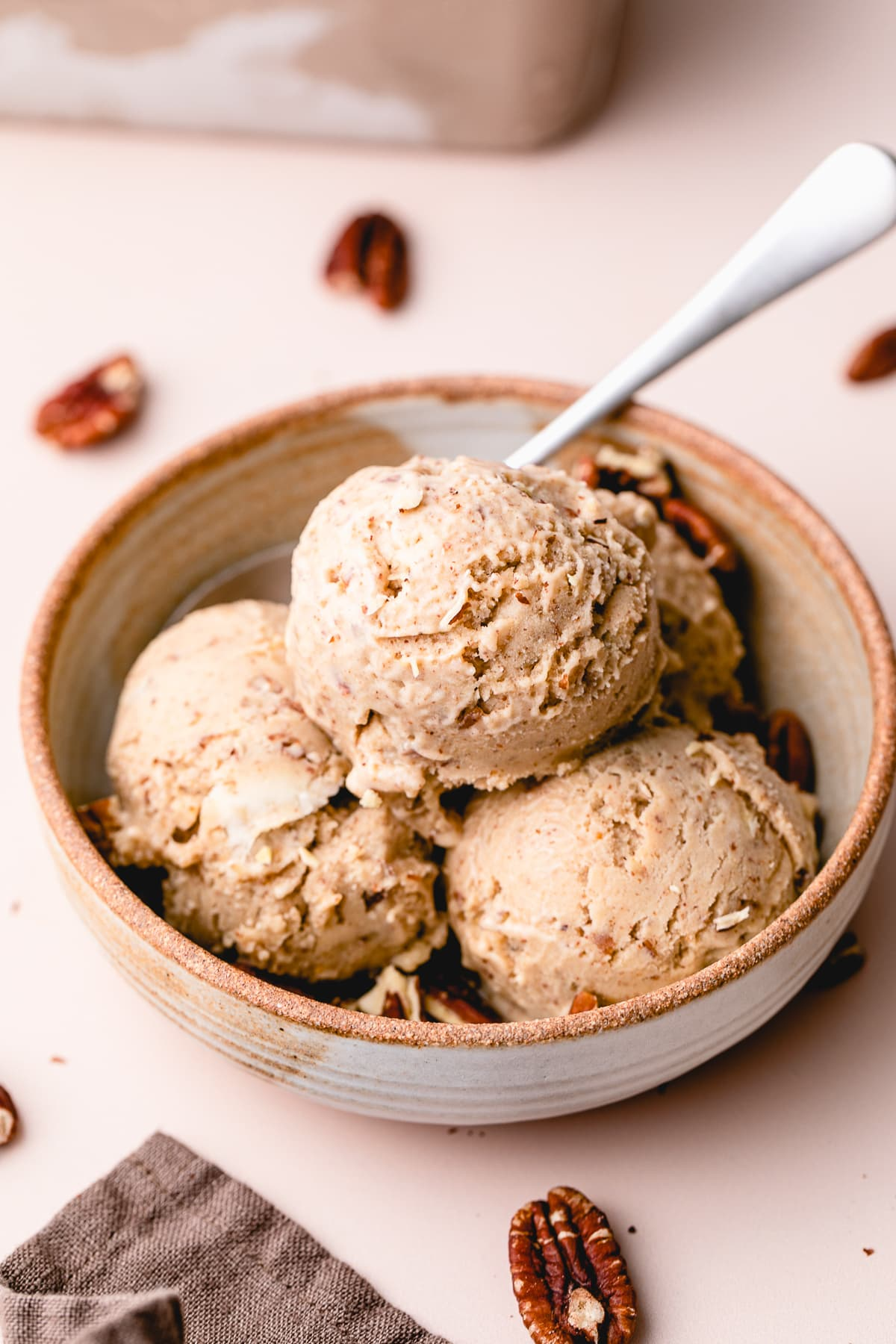 side angle view of healthy vegan butter pecan ice cream scoops in a bowl.
