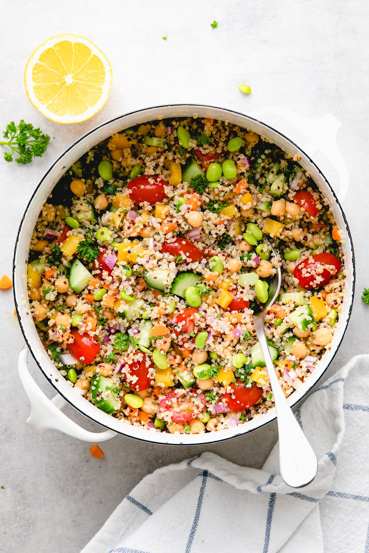 top down view of freshly made vegan quinoa salad in a pot with items surrounding.