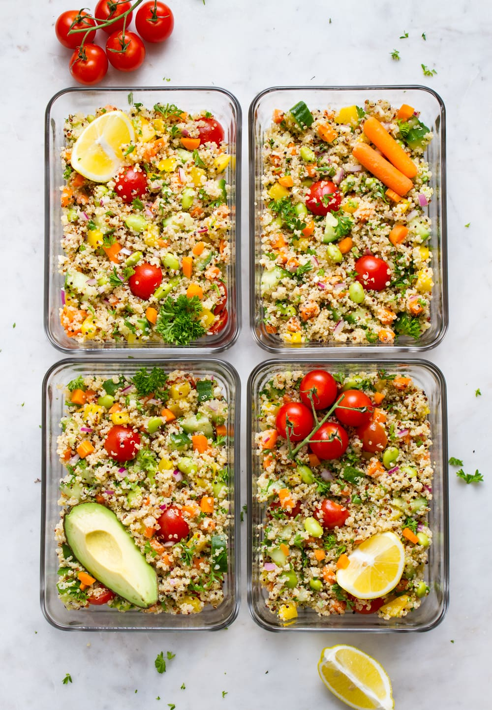 top down view of meal prepping quinoa salad in 4 rectangular glass containers.