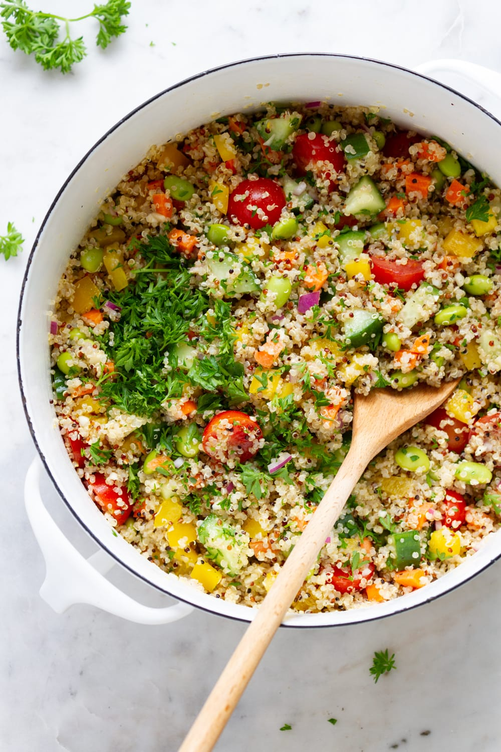 top down view of white pan with freshly mixed quinoa salad with parsley added.