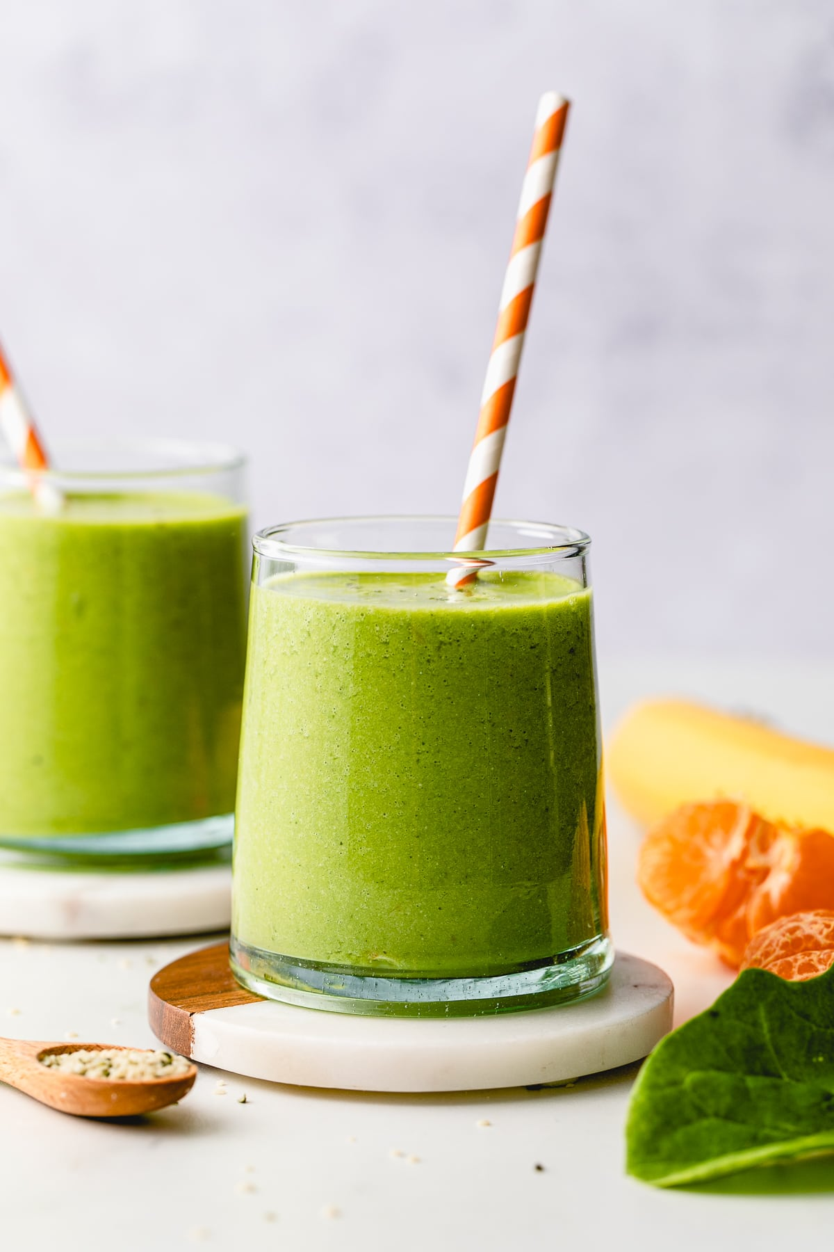 head on view of hemp smoothie in a glass with straw and items surrounding.