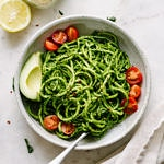 a top down view of a bowl of zucchini noodles tossed with spicy kale pesto and avocado and fork
