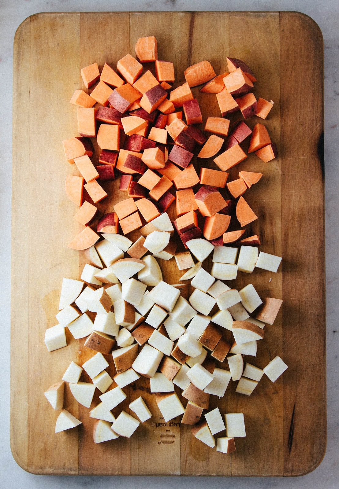 top down view of cubed sweet potatoes on a cutting board.