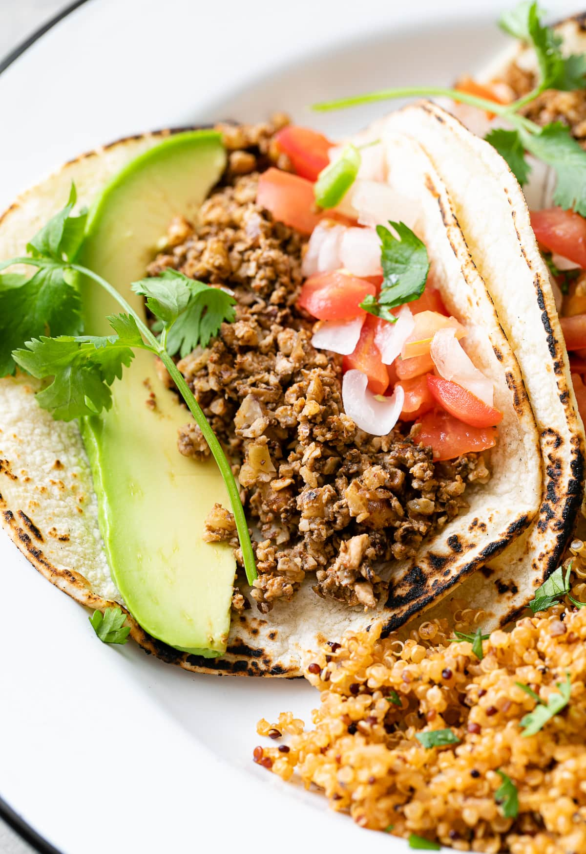 up close view of vegan street tacos with walnut meat on corn tortillas.