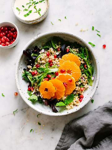 top down view of a rustic bowl with winter salad of quinoa, orange, pomegranates, and creamy orange-ginger cashew dressing