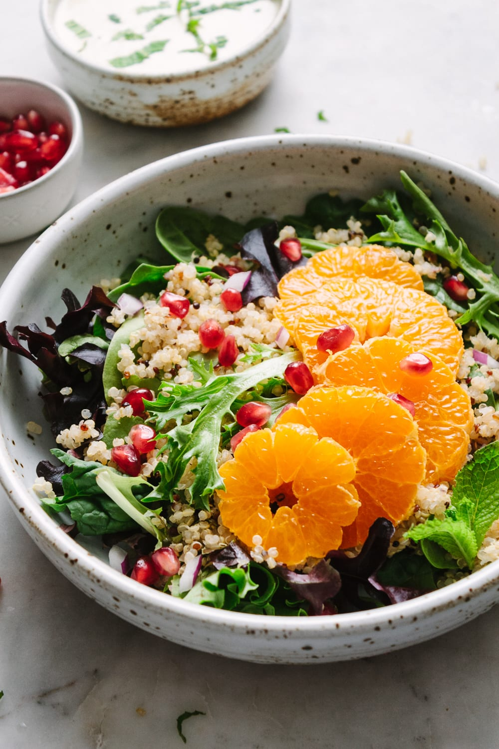side angle view of a rustic bowl with winter salad of quinoa, orange, pomegranates, and creamy orange-ginger cashew dressing