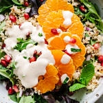 close up, top down view of a rustic bowl with winter salad of quinoa, orange, pomegranates, and creamy orange-ginger cashew dressing