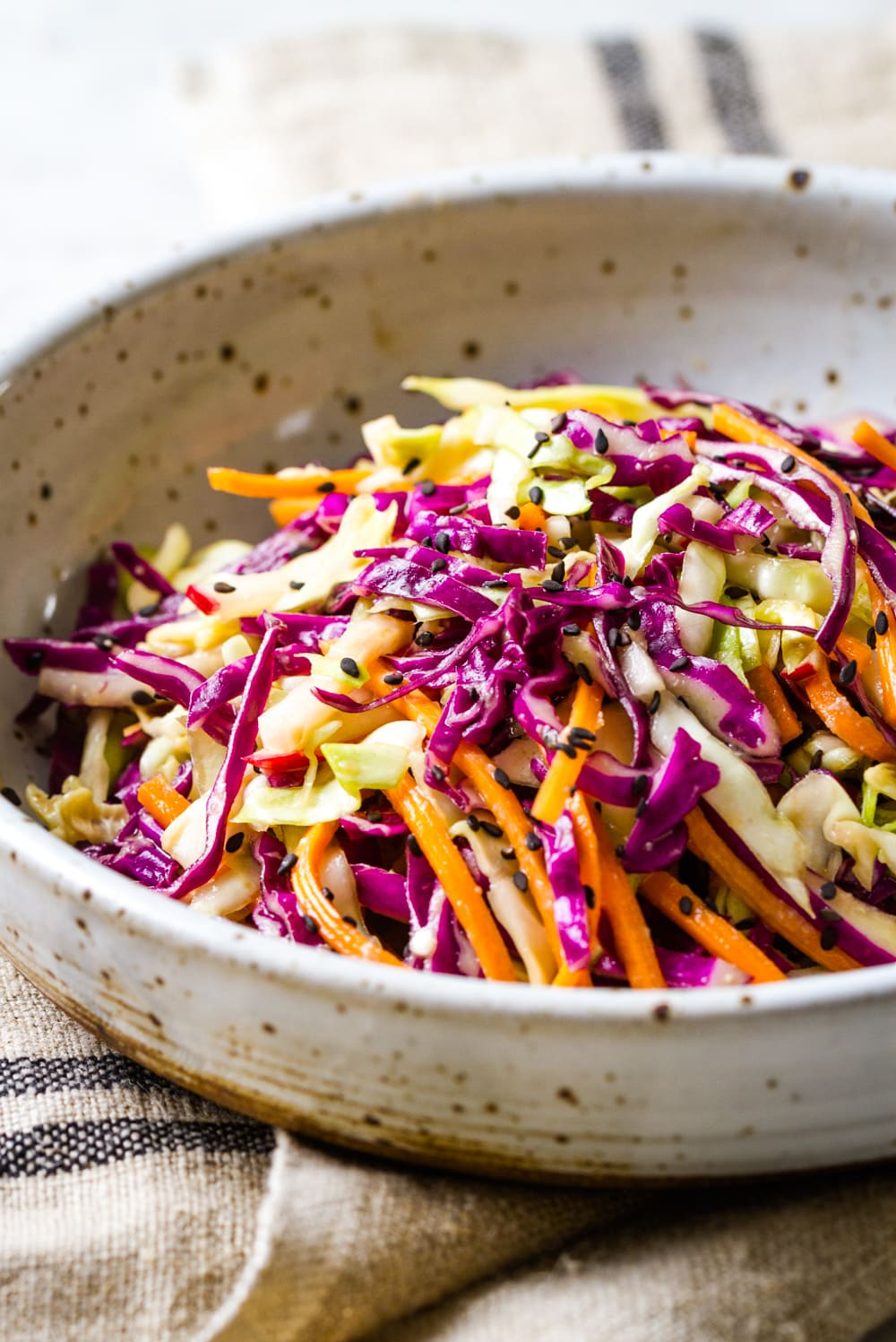 side angle view of a serving of crunchy asian slaw salad in a bowl.