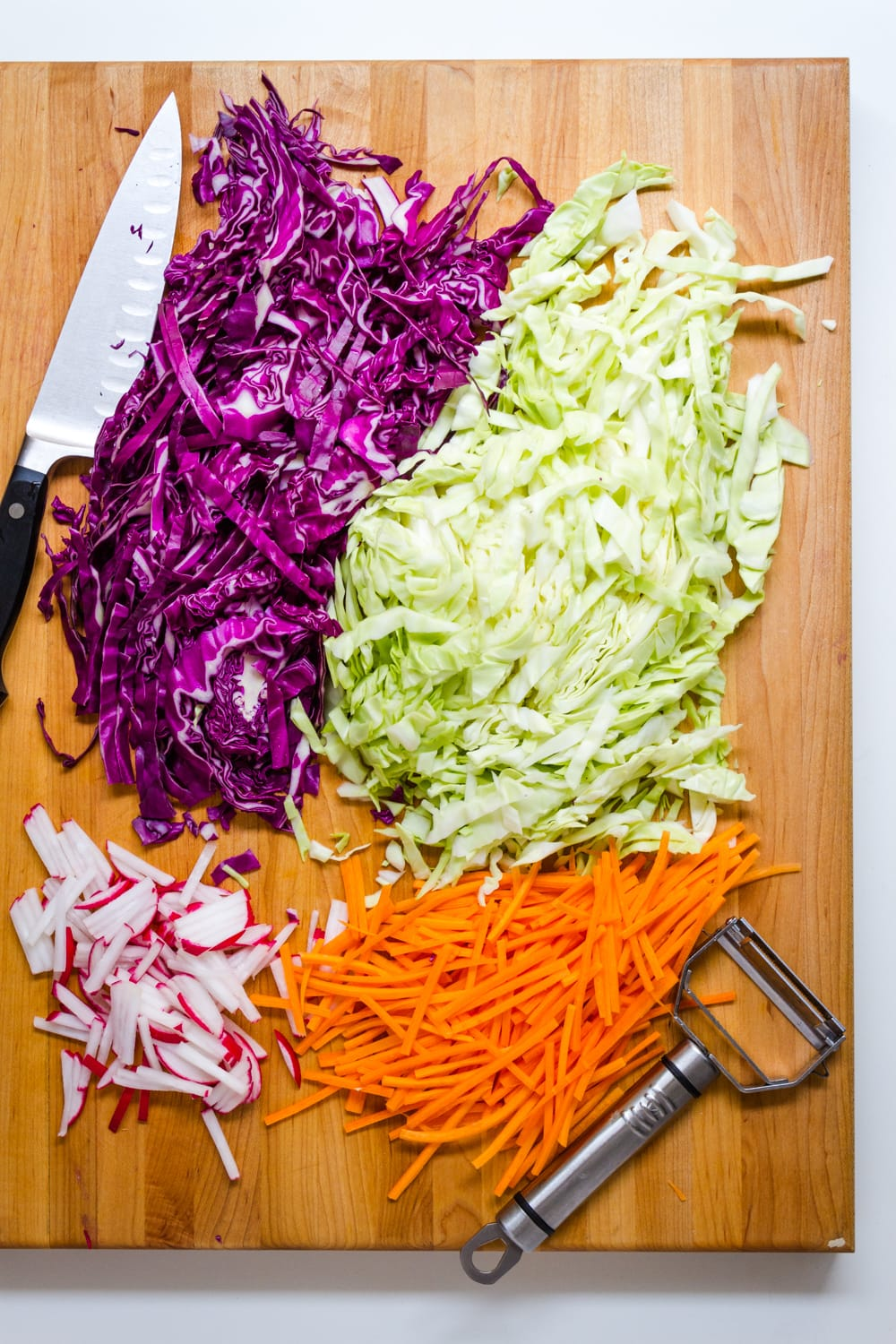 top down view of prepped ingredients for asian slaw salad on a wooden cutting board.