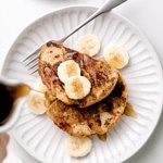 top down view of plated vegan banana french toast with syrup being poured over top.