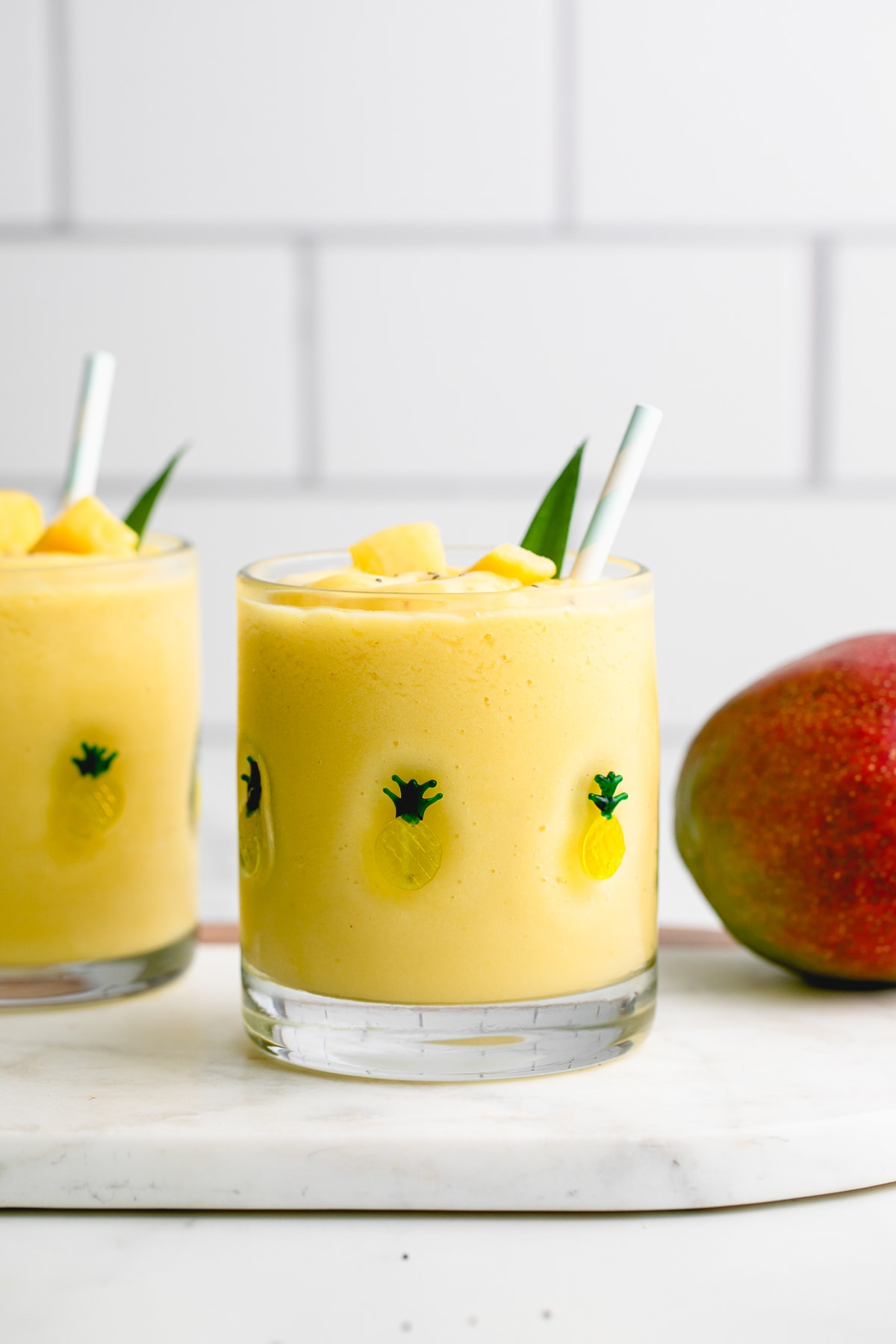 head on view of pineapple mango banana smoothie in a glass with items surrounding.