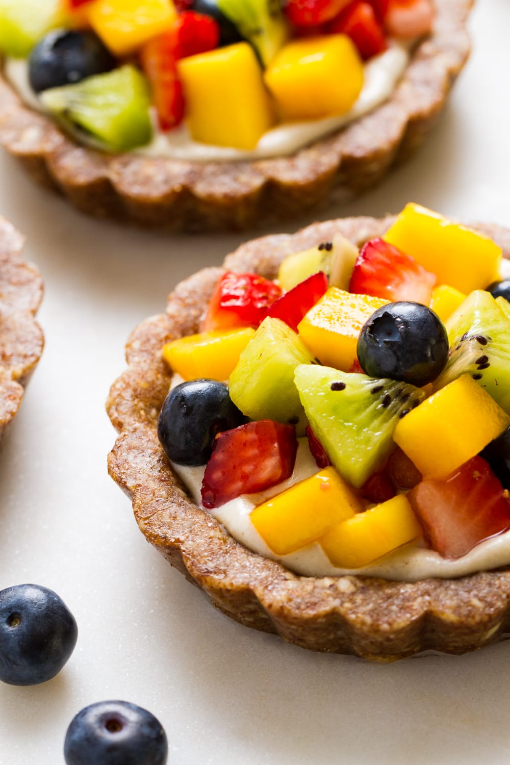 raw fruit tartlet on a marble serving board.