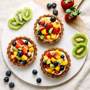 top down view of raw fruit tart on a circle marble serving board.