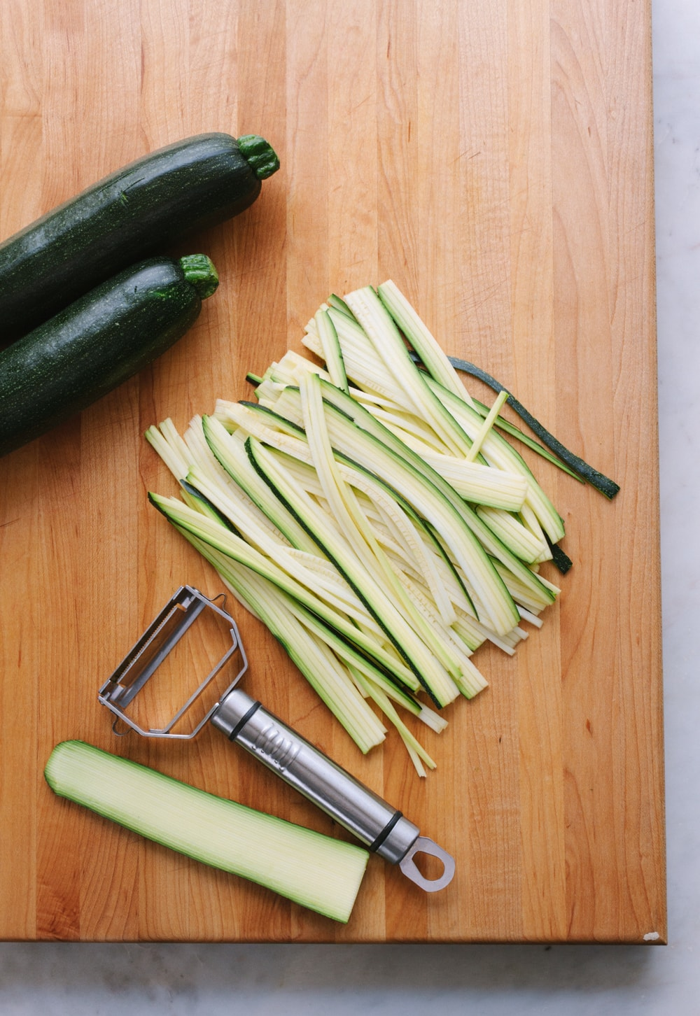 top down view of zucchini made into zucchini pasta noodles using a julienne tool on a wooden cutting board