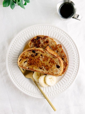 top down view of serving of vegan banana french toast on a white plate with fork.