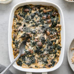 top down view of freshly baked vegan mushroom gratin with kale with a sprinkle of almond parmesan.