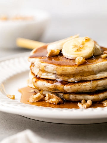 head on view of stacked almond flour banana gluten free pancakes on a plate with items surrounding.