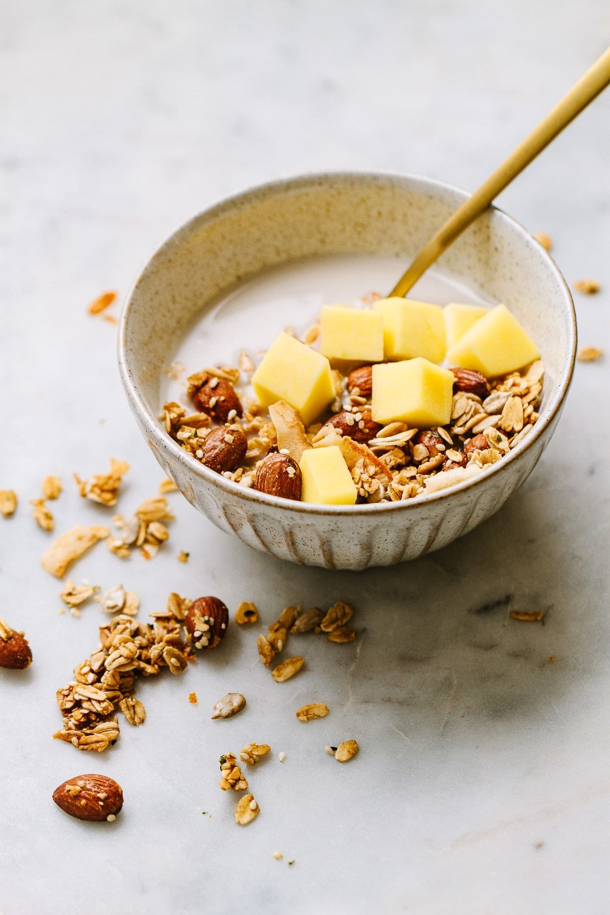side angle view of a small bowl with a serving of healthy orange ginger granola with cashew milk and diced mango with gold spoon.
