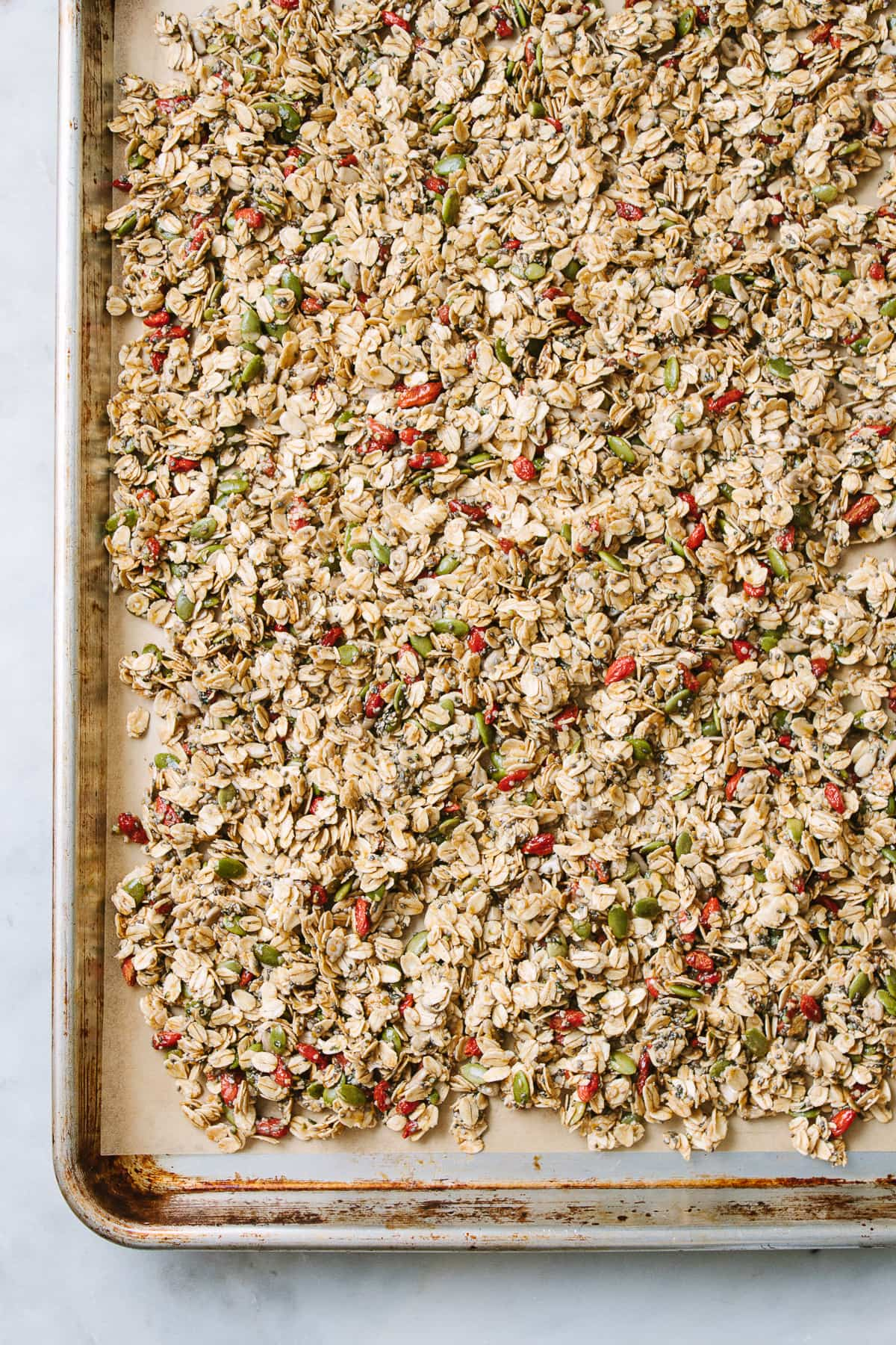top down view healthy granola layered on a baking sheet before going into the oven.
