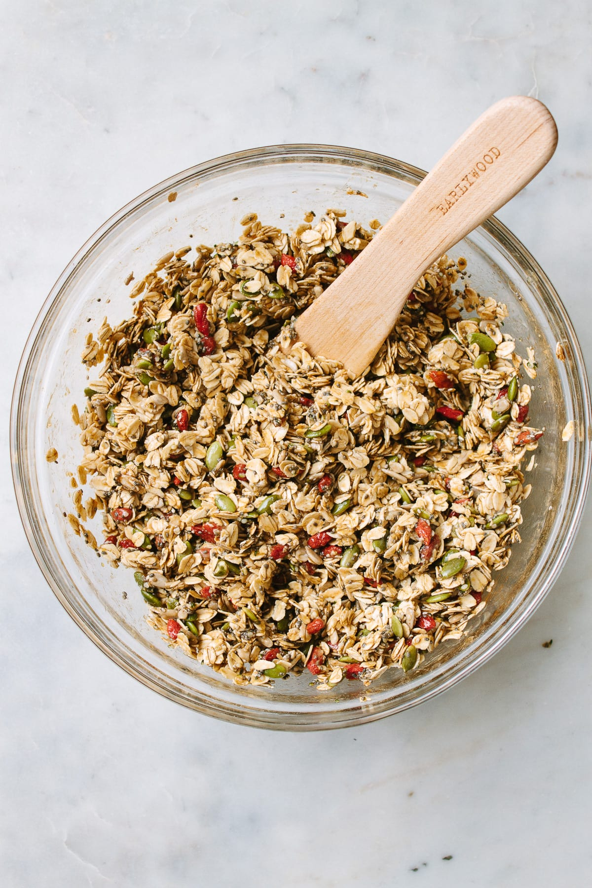 top down view of a glass mixing bowl with freshly mixed batch of seeds and goji berry granola.