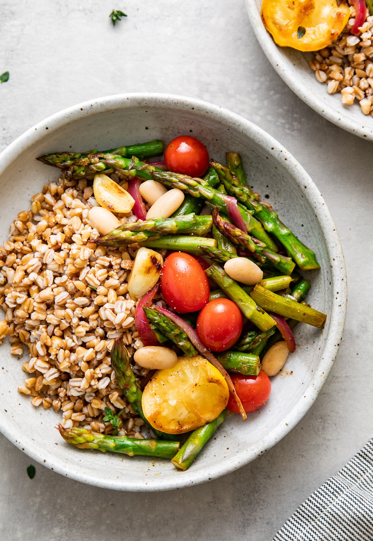 up close, top down view of a bowl with serving of skillet asparagus and tomato medley with farro and items surrounding.