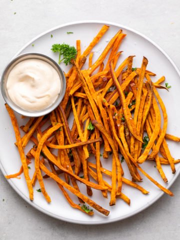 top down view of plate of freshly made baked crispy sweet potato shoestring fries.