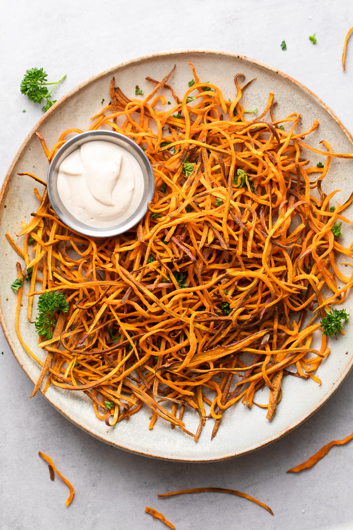 top down view of plate of freshly made baked crispy sweet potato shoestring fries curly style.