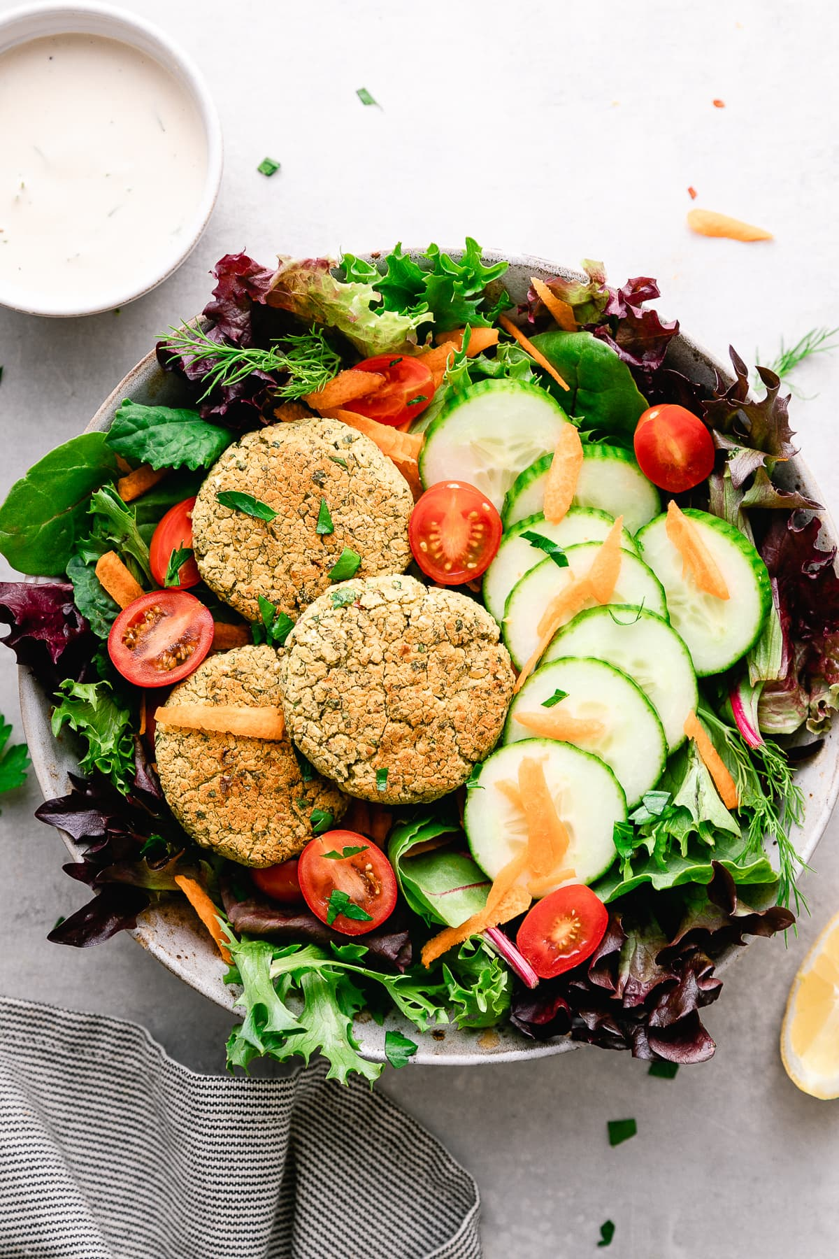top down view of baked falafel salad with items surrounding.