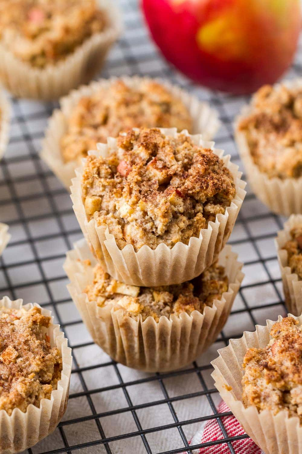 side angle view of a group of gluten free apple cinnamon muffins, with 2 stacked in the center on a wire cooling rack